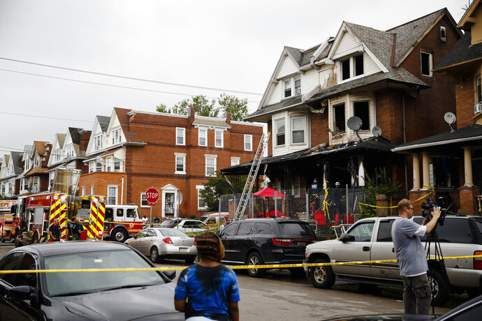 Firefighters work at the scene of the aftermath of a fire in Philadelphia, Tuesday, June 25, 2019. Several people, including some children, were injured trying to escape the house fire. (AP Photo/Matt Rourke)
