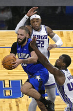Orlando Magic guard Evan Fournier (10) looks to pass the ball from between Sacramento Kings center Richaun Holmes (22) and forward Harrison Barnes (40) during the second half of an NBA basketball game Wednesday, Jan. 27, 2021, in Orlando, Fla. (AP Photo/Phelan M. Ebenhack)