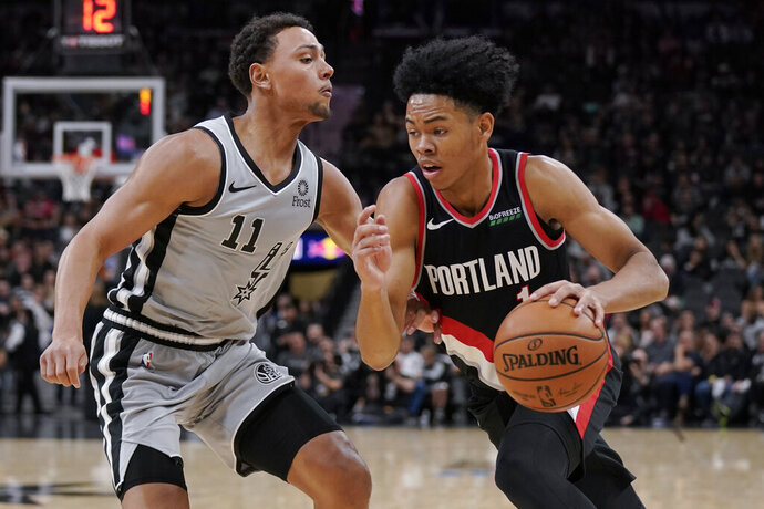 Portland Trail Blazers' Anfernee Simons, right, drives against San Antonio Spurs' Bryn Forbes during the first half of an NBA basketball game, Saturday, Nov. 16, 2019, in San Antonio. (AP Photo/Darren Abate)