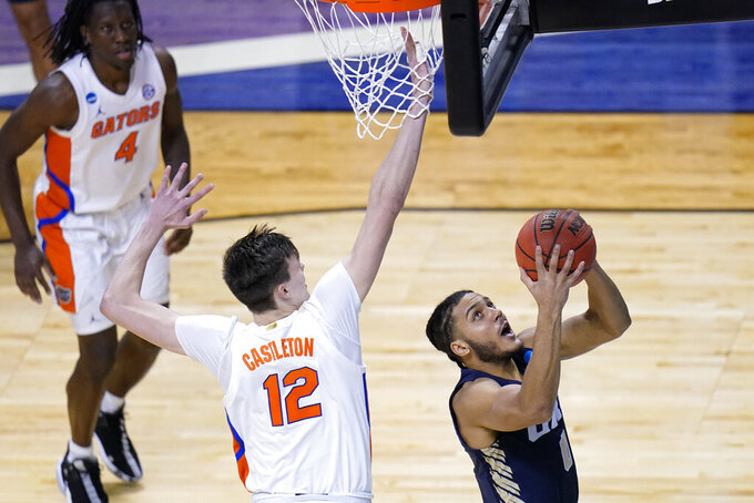 Oral Roberts forward Kevin Obanor (0) drives to the basket ahead of Florida forward Colin Castleton (12) during the second half of a college basketball game in the second round of the NCAA tournament at Indiana Farmers Coliseum, Sunday, March 21, 2021 in Indianapolis. (AP Photo/AJ Mast)