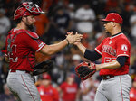 Los Angeles Angels relief pitcher Hansel Robles, right, shakes hands with catcher Kevan Smith following the team's win over the Houston Astros in a baseball game, Saturday, Sept. 21, 2019, in Houston. (AP Photo/Eric Christian Smith)