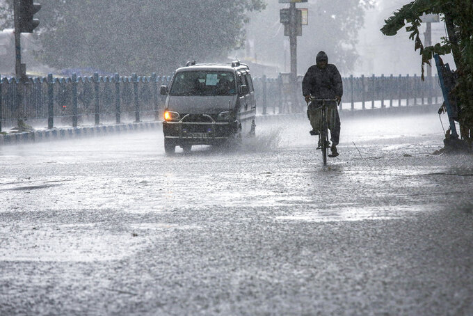 A man pedals through heavy rain under the inclement weather due to Cyclone Yaas in Kolkata, India, Wednesday, May 26, 2021. Heavy rain and a high tide lashed parts of India's eastern coast as a cyclone pushed ashore Wednesday in an area where more than 1.1 million people have evacuated amid a devastating coronavirus surge. (AP Photo/Bikas Das)