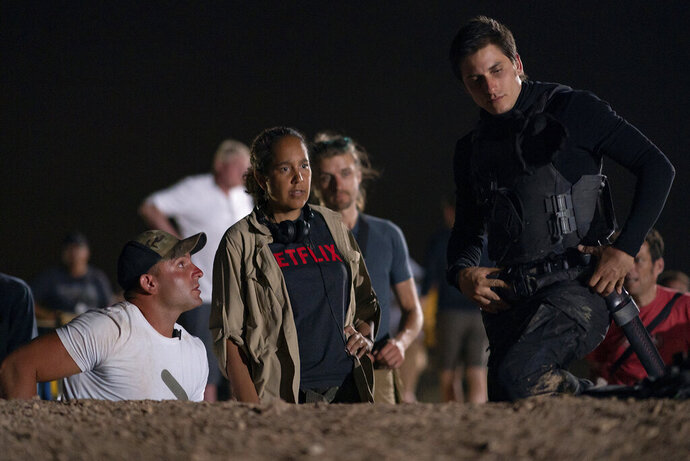 This image released by Netflix shows director Gina Prince-Bythewood, center, with actor Luca Marinelli, right, during the filming of