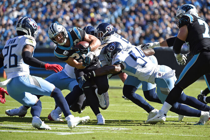 Carolina Panthers running back Christian McCaffrey (22) runs the ball while Tennessee Titans cornerback Logan Ryan (26) and inside linebacker Rashaan Evans (54) move in to tackle during the first half of an NFL football game in Charlotte, N.C., Sunday, Nov. 3, 2019. (AP Photo/Mike McCarn)