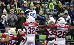 Seattle Seahawks fans react after Arizona Cardinals middle linebacker Jordan Hicks, lower left, recovered a fumble during the second half of an NFL football game, Sunday, Dec. 22, 2019, in Seattle. (AP Photo/Lindsey Wasson)