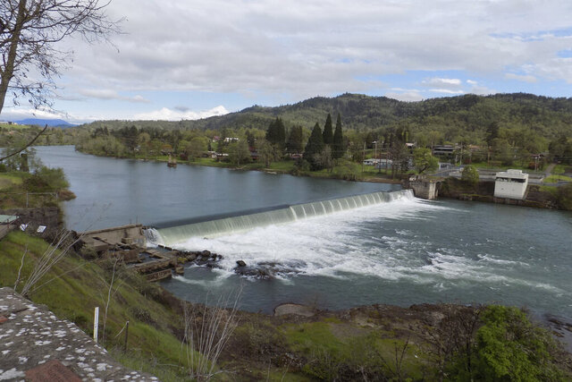 This photo provided by Jim McCarthy shows the Winchester Dam in Winchester, Ore., on April 19, 2019. Environmental and fishing groups are suing a small, private water district in southern Oregon over the 130-year-old dam on a pristine stretch of the North Umpqua River. The lawsuit, filed in U.S. District Court in Eugene, asks a judge to order the Winchester Water Control District to build a new fish ladder on the Winchester Dam and make major repairs to the overall dam, which is on a national historic registry. (JimMcCarthy/WaterWatch via AP)