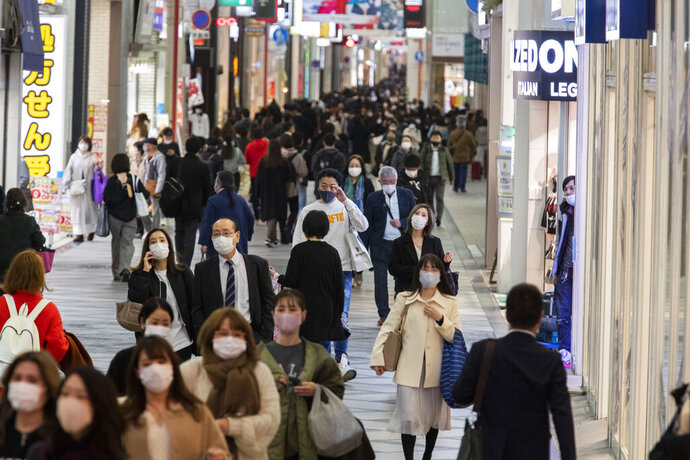 People wearing face masks to help curb the spread of the coronavirus walk through a shopping street in Osaka, western Japan, Thursday, Nov. 26, 2020. (AP Photo/Hiro Komae)