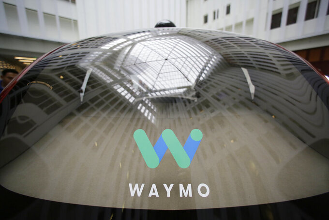 FILE - In this Dec. 13, 2016, file photo, a skylight is reflected in the rear window of a Waymo driverless car during a Google event in San Francisco. The latest challenge for the autonomous vehicle industry: How to assure passengers that the car they are getting in is virus free, even if it doesn't have a driver. An executive with Waymo said Wednesday, June 17, 2020 that the coronavirus pandemic forced it to put its limited ride service in the Phoenix area on hold to make sure human backup drivers and passengers were safe. (AP Photo/Eric Risberg, File)