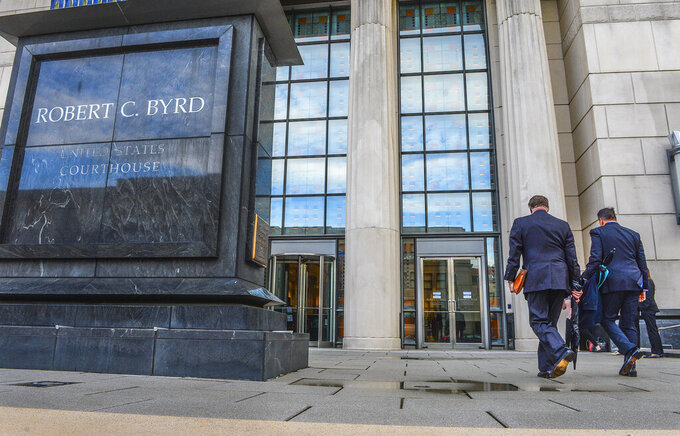 Huntington Mayor Steve Williams, left, and lawyer Rusty Webb enter the Robert C. Byrd United States Courthouse in Charleston, W. Va., Monday, May 3, 2021, for the start of the opioid trial. The trial is set to start in a lawsuit filed in West Virginia accusing three drug distributors of fueling a local opioid epidemic with excessively large shipments of painkillers over several years. (Kenny Kemp/Charleston Gazette-Mail via AP)