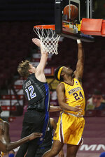 Minnesota's Eric Curry (24) makes a basket against Saint Louis's Marten Linssen (12) during an NCAA college basketball game Sunday, Dec. 20, 2020, in Minneapolis. (AP Photo/Stacy Bengs)