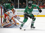 Dallas Stars center Joe Pavelski (16) tries to gain control of the puck in front of Calgary Flames goaltender David Rittich (33) during the first period of an NHL hockey game in Dallas, Thursday, Oct. 10, 2019. (AP Photo/Michael Ainsworth)