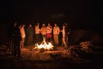 In this Sunday, Jan. 12, 2020 photo, Dakar pilots and medics gather around a bonfire after stage seven of the Dakar Rally in Wadi Al Dawasir, Saudi Arabia. Formerly known as the Paris-Dakar Rally, the race was created by Thierry Sabine after he got lost in the Libyan desert in 1977. Until 2008, the rallies raced across Africa, but threats in Mauritania led organizers to cancel that year's event and move it to South America. It has now shifted to Saudi Arabia. The race started on Jan. 5 with 560 drivers and co-drivers, some on motorbikes, others in cars or in trucks. Only 41 are taking part in the Original category. (AP Photo/Bernat Armangue)