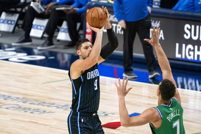 Orlando Magic center Nikola Vucevic (9) shoots a three-point basket over Dallas Mavericks center Dwight Powell (7) during the first half of an NBA basketball game, Saturday, Jan. 9, 2021, in Dallas. (AP Photo/Jeffrey McWhorter)
