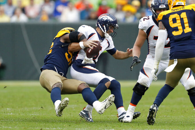 Denver Broncos quarterback Joe Flacco, right, is sacked by Green Bay Packers linebacker Rashan Gary during the second half of an NFL football game Sunday, Sept. 22, 2019, in Green Bay, Wis. (AP Photo/Matt Ludtke)