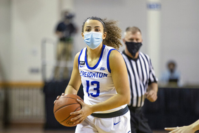 In this photo provided by Creighton Athletics, Creighton guard Rachael Saunders plays during a women's NCAA college basketball game against Drake in Omaha, Nebraska, on Wednesday, Nov. 25, 2020. Official Tom Danaher is at rear. The DePaul and Creighton women's basketball teams are among a few squads that have taken it a step further with their players wearing masks while on the court playing. (Catherine Grosdidier/Creighton Athletics via AP)