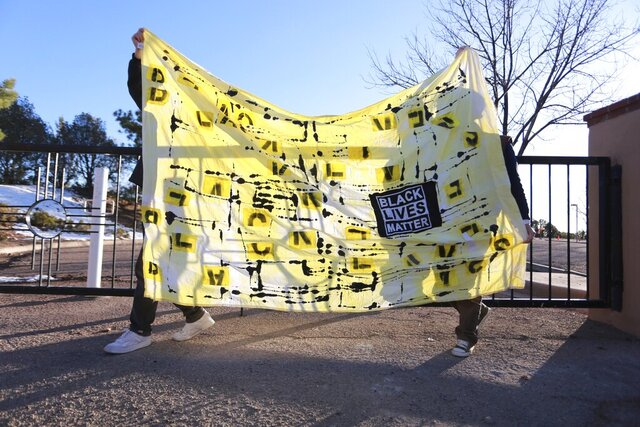 Protesters carry a banner in front of the official residence of Gov. Michelle Lujan Grisham as part of an in-person and virtual for justice in the police shooting of a Black man two weeks earlier on Friday, Dec. 4, 2020, in Santa Fe, N.M. Family of Rodney Applewhite, 25, have been asking for additional details in the incident that led to him being shot by police. New Mexico State Police released additional information after the protest, and released his name to the public. Applewhite, of South Bend, Indiana, was driving through New Mexico on the way to a family Thanksgiving in Phoenix, Arizona, when police shot him on Nov. 19, his family said. (AP Photo/Cedar Attanasio)