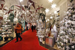 FILE - In this Tuesday, Nov. 5, 2019 file photo shoppers browse the Holiday Lane section at the Macy's flagship store, in New York. Macy's cut its profit and sales expectations for the year after posting its first comparable store sales decline in almost two years, Thursday, Nov. 21. The company is citing the late arrival of colder weather, meager tourist business, weak traffic at some malls and problems on its website.  (AP Photo/Richard Drew, File)