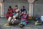 Daily wage laborers wearing masks as a precaution against the coronavirus wait to be hired for work by a roadside in Kochi, Kerala state, India, Friday, Nov. 20, 2020. India's total number of coronavirus cases since the pandemic began crossed 9 million on Friday. (AP Photo/R S Iyer)