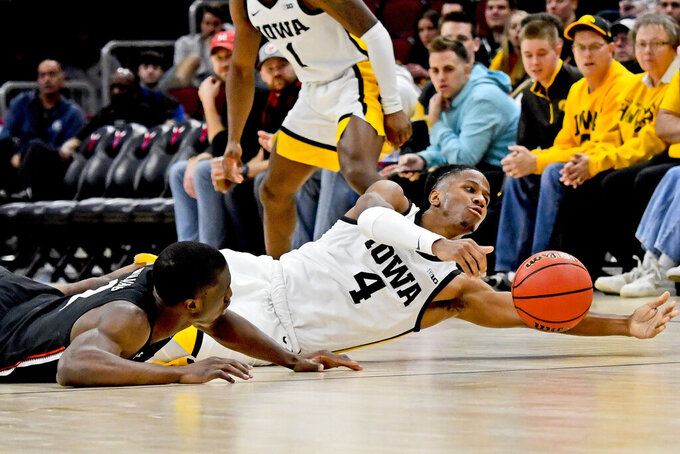 Cincinnati guard Keith Williams, left, fights for a loose ball with Iowa guard Bakari Evelyn (4) during the second half of an NCAA college basketball game Saturday, Dec. 21, 2019, in Chicago. (AP Photo/Matt Marton)