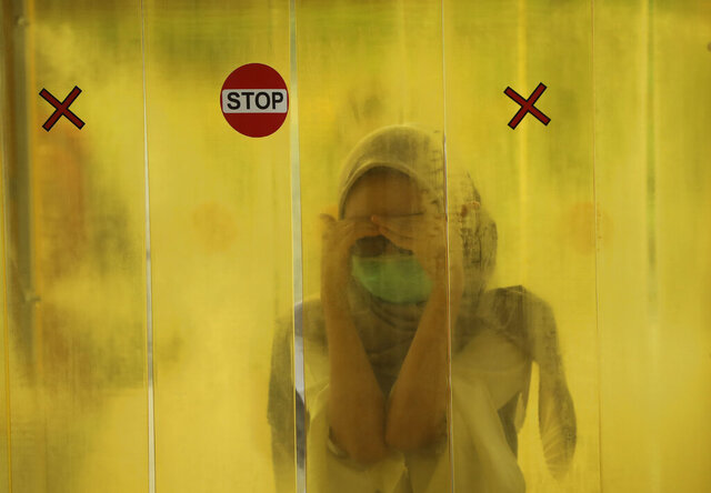 A woman reacts as she is sprayed with disinfectant inside a chamber as a precaution against the new coronavirus outbreak before entering a shopping mall in Jakarta, Indonesia, Tuesday, June 9, 2020. As Indonesia's overall virus caseload continues to rise, the capital city has moved to restore normalcy by lifting some restrictions this week, saying that the spread of the virus in the city of 11 million has slowed after peaking in mid-April. (AP Photo/Dita Alangkara)