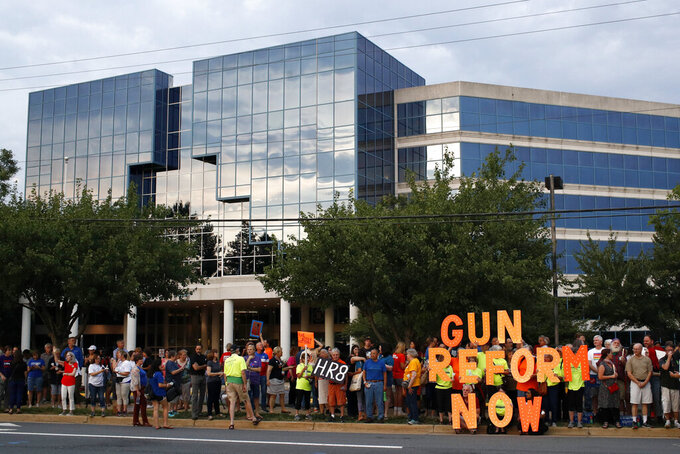 FILE - In this Aug. 5, 2019, file photo, people gather at a vigil for recent victims of gun violence outside the National Rifle Association's headquarters building in Fairfax, Va. The NRA has been embroiled in a legal and financial battle that liberals have cheered as the potential downfall of the powerful gun rights lobby, opening up a wide path for reform. Not so fast. While the battle over gun rights is shifting from Washington to the states, the NRA's message has become so solidified in the Republican political fabric that it's self-sustaining, even if the gun rights organization that led the way ceases to exist, leaders on both sides say. (AP Photo/Patrick Semansky, File)