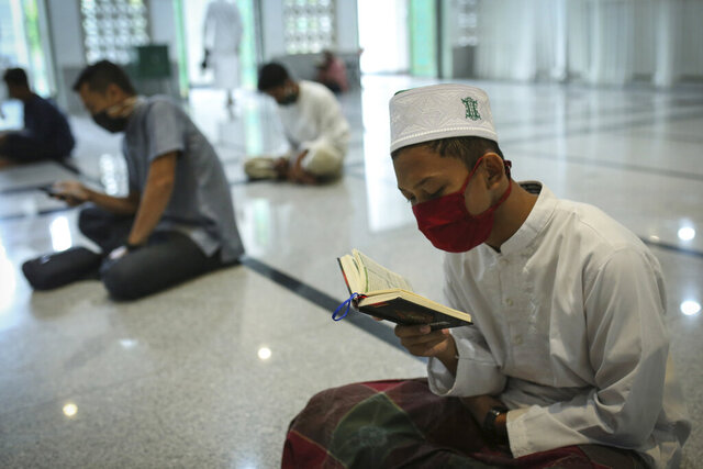 Muslim men wearing face masks as a precaution against coronavirus men read the holy book of Quran during the first day of the holy fasting month of Ramadan at a mosque in the religiously conservative province of Aceh, Indonesia, Friday, April 24, 2020. During Ramadan, which begins Friday, faithful Muslims normally fast during the day and then congregate for night prayers and share communal meals. (AP Photo/Heri Juanda)