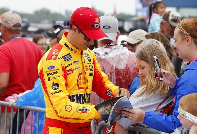 Joey Logano signs autographs before the NASCAR cup series auto race at Michigan International Speedway, Sunday, June 9, 2019, in Brooklyn, Mich. (AP Photo/Carlos Osorio)