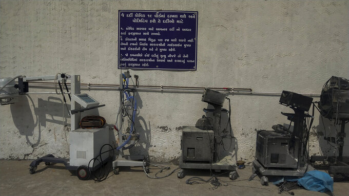 Instructions for COVID-19 patients are seen on a signage in Gujarati next to damaged equipments after a deadly fire at the Welfare Hospital in Bharuch, western India, Saturday, May 1, 2021. The fire in a COVID-19 ward of the hospital killed multiple patients early Saturday, as the country grappling with the worst outbreak yet steps up a vaccination drive for all its adults even though some states say don't have enough jabs.  (AP Photo/Viral Rana)