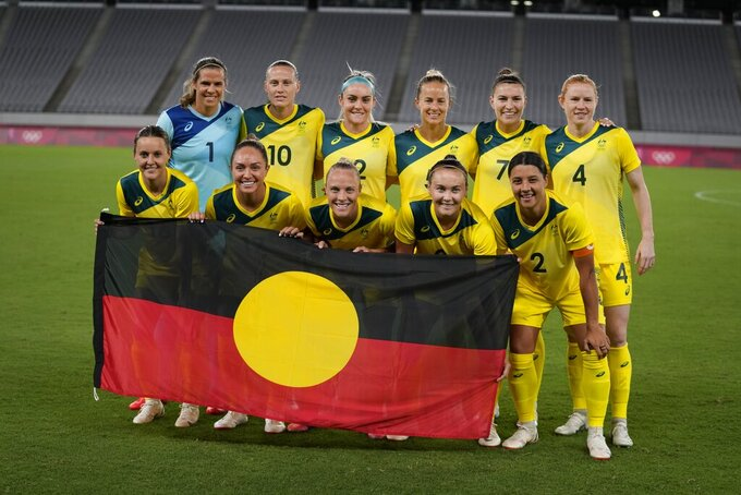 Australia players pose for a group photo with an indigenous flag prior to women's soccer match against New Zealand at the 2020 Summer Olympics, Wednesday, July 21, 2021, in Tokyo. (AP Photo/Ricardo Mazalan)
