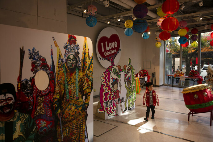 In this Feb. 13, 2020, photo, a boy walks around an information center in Yokohama's Chinatown, near Tokyo. A top Olympic official made clear Friday the 2020 Games in Tokyo will not be cancelled despite the virus that has spread from China. (AP Photo/Jae C. Hong)