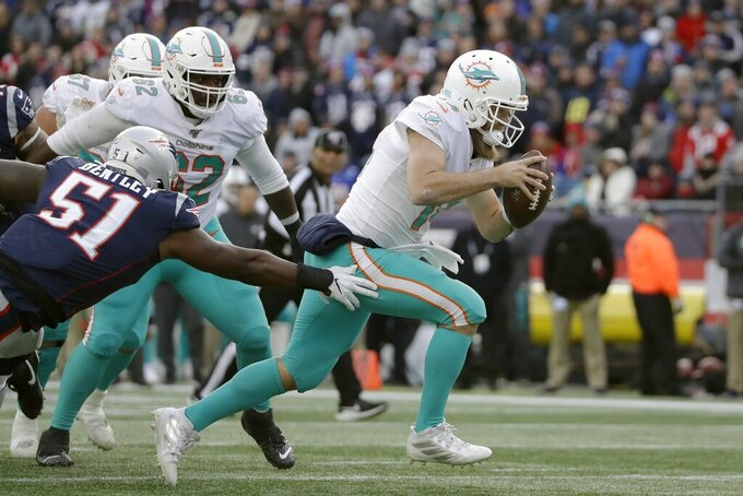 Miami Dolphins quarterback Ryan Fitzpatrick runs past New England Patriots linebacker Ja'Whaun Bentley, left, on the way to a touchdown in the second half of an NFL football game, Sunday, Dec. 29, 2019, in Foxborough, Mass. (AP Photo/Elise Amendola)