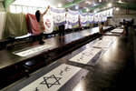 In this Saturday, Feb. 8, 2020 photo, workers print Israeli flags with a slogan in Persian which reads,