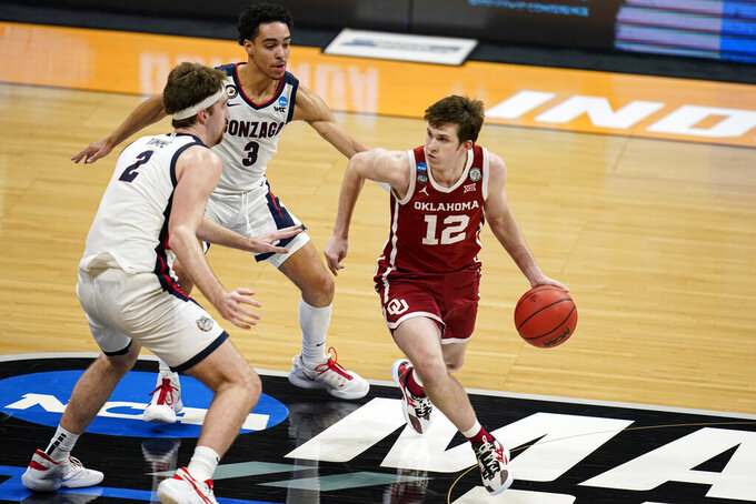 Oklahoma guard Austin Reaves (12) tries to get past Gonzaga forward Drew Timme (2) and guard Andrew Nembhard (3) in the first half of a second-round game in the NCAA men's college basketball tournament at Hinkle Fieldhouse in Indianapolis, Monday, March 22, 2021. (AP Photo/Michael Conroy)