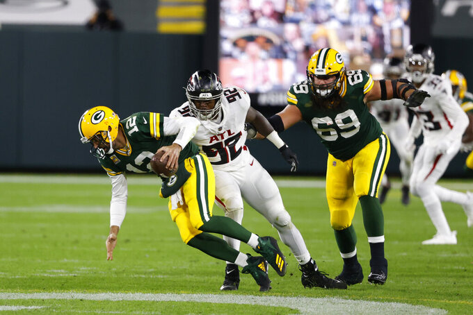 Green Bay Packers quarterback Aaron Rodgers (12) is tackled by Atlanta Falcons' Charles Harris (92) during the second half of an NFL football game, Monday, Oct. 5, 2020, in Green Bay, Wis. (AP Photo/Tom Lynn)