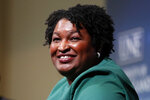 """FILE - Stacey Abrams, a Georgia Democrat who has launched a multimillion-dollar effort to combat voter suppression, speaks at the University of New England in Portland, Maine on Jan. 22, 2020.  Berkley announced Tuesday that it had acquired rights to three out-of-print novels by Abrams that she had written nearly 20 years ago under the name Selena Montgomery. Berkley, a Penguin Random House imprint, will begin reissuing the books; """"Rules of Engagement,"""" """"The Art of Desire"""" and """"Power of Persuasion,"""" in 2022. (AP Photo/Robert F. Bukaty, File)"""