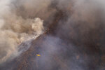 A seaplane flies over a wildfire near the town of Jubrique, in Malaga province, Spain, Monday, Sept. 13, 2021. Firefighting crews in southern Spain are looking at the sky for much-needed rainfall they hope can help extinguish a stubborn mega-fire that has ravaged 7,400 hectares (18,300 acres) in five days and displaced just under 3,000 people from their homes. Authorities are describing the blaze in Sierra Bermeja, a mountain range in the Malaga province, as a sixth-generation fire of the extreme kind brought by the shifting climate on the planet. (AP Photo/Pedro Armestre)