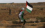A masked protester waves his national flag near the fence of Gaza Strip border with Israel during a protest east of Gaza City, Friday, Nov. 9, 2018. Gaza's Hamas rulers said Friday that deadly protests along Gaza-Israel perimeter fence have achieved some goals; $15 million from Qatar to help pay the salaries of civil servants. (AP Photo/Adel Hana)