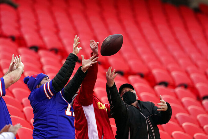 Fans fight to catch a football thrown by Buffalo Bills wide receiver Stefon Diggs before the AFC championship NFL football game between the Kansas City Chiefs and the Buffalo Bills, Sunday, Jan. 24, 2021, in Kansas City, Mo. (AP Photo/Charlie Riedel)