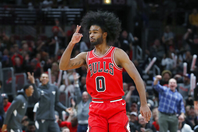 Chicago Bulls' Coby White signals scoring another three-point basket during the second half of an NBA basketball game against the New York Knicks Tuesday, Nov. 12, 2019, in Chicago. The Bulls won 120-102. (AP Photo/Charles Rex Arbogast)