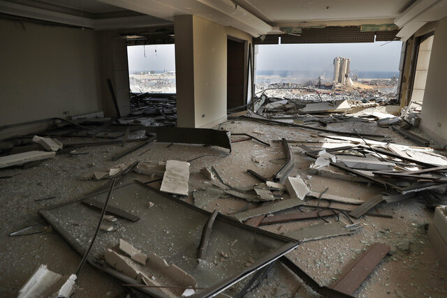 The scene of the explosion that hit the seaport of Beirut is seen through a damaged apartment in Beirut, Lebanon, Wednesday, Aug. 5, 2020. Prime Minister Hassan Diab, in a short televised speech, has appealed to all countries and friends of Lebanon to extend help to the small nation, saying: