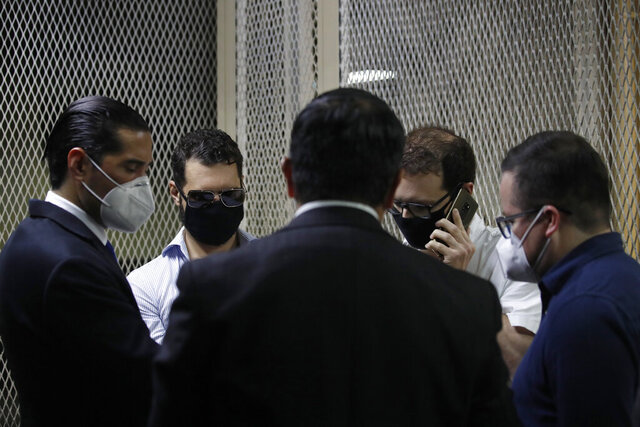 The sons of former Panamanian President Ricardo Martinelli, Ricardo Martnelli Linares, center left, and his brother Luis Enrique Martinelli Linares, center right, are accompanied by their lawyers before a hearing at the judicial court building in Guatemala City, Monday, July 6, 2020. Guatemalan police detained the Martinelli brothers on an Interpol warrant for money laundering, as they attempted to board a private plane out of the country. (AP Photo/Moises Castillo)