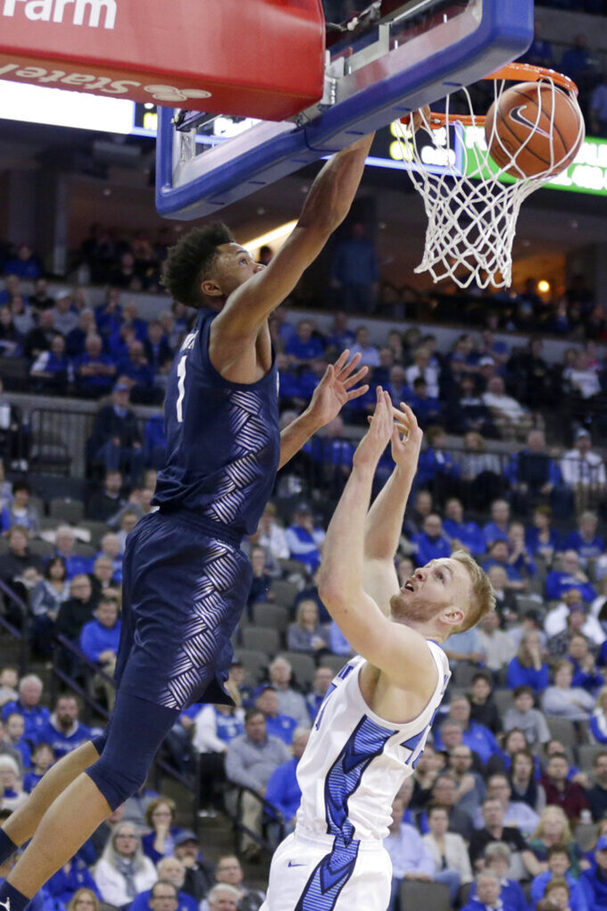 Georgetown's Jamorko Pickett (1) dunks over Creighton's Kelvin Jones (43) during the first half of an NCAA college basketball game in Omaha, Neb., Wednesday, March 4, 2020. (AP Photo/Nati Harnik)