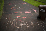 Splattered paint and chalk writing are on the driveway of the home of fired Minneapolis police Officer Derek Chauvin in Oakdale, Minn., Wednesday, May 27, 2020. The mayor of Minneapolis called Wednesday for criminal charges against Chauvin, the white police officer seen on video kneeling against the neck of Floyd George, a handcuffed black man who complained that he could not breathe and died in police custody. (Jeff Wheeler/Star Tribune via AP)