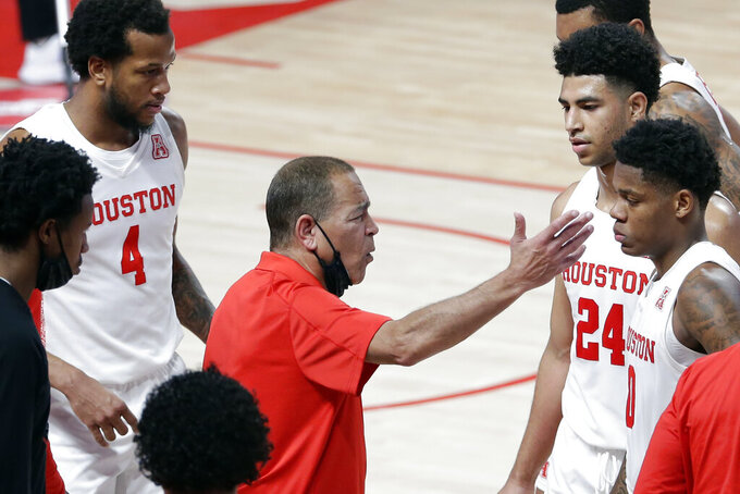 Houston head coach Kelvin Sampson, center, talks with his players during a time out against Central Florida during the first half of an NCAA college basketball game Sunday, Jan. 17, 2021, in Houston. (AP Photo/Michael Wyke)