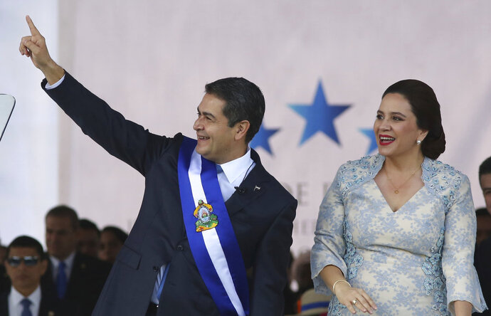 FILE - In this Jan. 27, 2018 file photo, Honduran President Juan Orlando Hernandez acknowledges supporters accompanied by his wife Ana Garcia, during his presidential inaugural ceremony at the National Stadium in Tegucigalpa, Honduras. Prosecutors in Honduras accusing politicians and officials on June 13, 2018 of having diverted millions in government funds to political parties, including Hernandez's 2013 campaign.  (AP Photo/Fernando Antonio, File)
