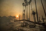FILE - In this Dec. 5, 2017 file photo, smoke rises behind a destroyed apartment complex as a the Thomas wildfire burns in Ventura, Calif. New California data shows insurance companies declined to renew nearly 350,000 home insurance policies in areas at high risk for wildfire since the state began collecting data in 2015. Insurance officials say many people likely found coverage elsewhere, though potentially at higher cost. (AP Photo/Noah Berger, File)