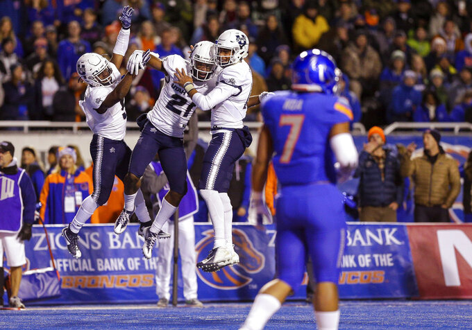 Utah State wide receiver Jalen Greene (21) celebrates with running back Darwin Thompson, left, and quarterback Jordan Love after a touchdown reception during the first half of an NCAA college football game against Boise State on Saturday, Nov. 24, 2018, in Boise, Idaho. (AP Photo/Steve Conner)