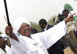 FILE - In this May 1, 2010 file photo, then Sudanese President Omar el-Bashir greets his supporters during a rally at a fair in Khartoum, Sudan. A Sudanese official and a former minister said Wednesday, April, 17, 2019, that the military has transferred ousted President Omar al-Bashir to the city's Kopar Prison in Khartoum. The move came after organizers of the street protests demanded the military move al-Bashir to an official prison. (AP Photo/Abd Raouf, File)