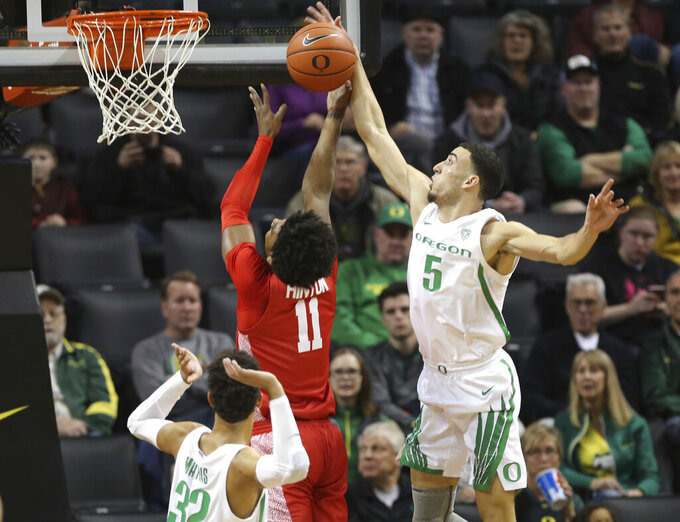 Oregon's Chris Duarte, right, blocks a shot by Houston's Nate Hinton, center, with Oregon's Anthony Mathis at lower left during the first half of an NCAA college basketball game in Eugene, Ore., Friday, Nov. 22, 2019. (AP Photo/Chris Pietsch)