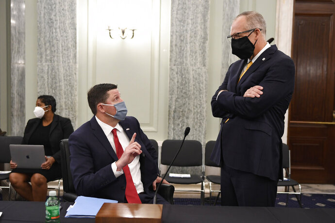 University of Mississippi Vice Chancellor for Intercollegiate Athletics Keith Carter, left, talks with Southeastern Conference Commissioner Greg Sankey, right, before they testify at a Senate Commerce Committee hearing on Capitol Hill in Washington, Wednesday, July 1, 2020. The hearing is looking at the National Collegiate Athletic Association Board of Governors' recent report on student-athlete compensation and the modernization of rules related to name, image, and likeness (NIL) commercialization. (AP Photo/Susan Walsh)